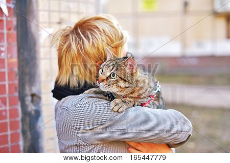 girl in glasses with a cat in her arms in the street