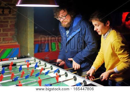 Two young men in evening bar play kicker. A friend with a beard and the other in the yellow jacket. They are concentrated.