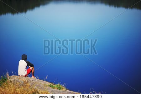 Young man sitting on the stone enjoying peaceful moment