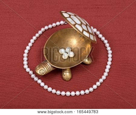 Decorative turtle jewelry box and freshwater white pearl necklace on red fabric backboard
