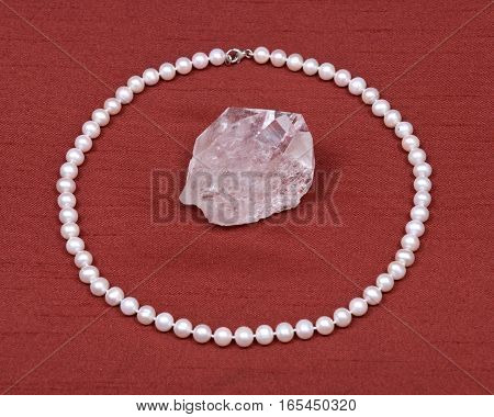 Freshwater white pearl necklace and crystal quartz gemstone on red fabric background