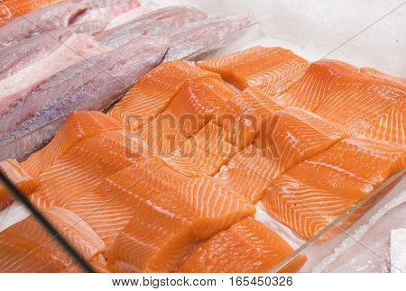 Close-up of raw, fresh salmon fillets on ice