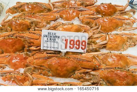 Close-up of cooked blue swimmer crabs on ice with price tag