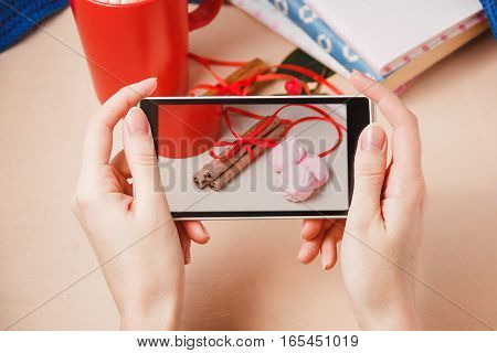 woman taking photo of red mug of hot chocolate drink with marshmallow, beze and cinamon on wooden background