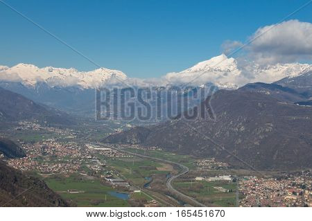 View of Val di Susa with its villages and snowy Alps on background. Piedmont. Italy