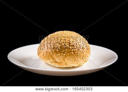 Bun with sesame seeds in white dish isolated on black background