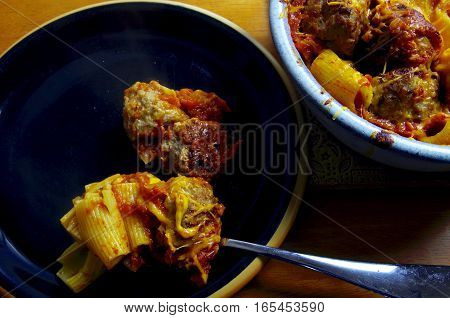 A black dinner plate is shown with a serving of baked rigatoni and meatballs. The serving spoon is on the plate and a blue casserole with more pasta and meatballs is to the side.