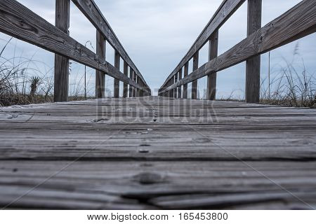 Low Angle View of Boardwalk over Dunes leads to the gulf coast