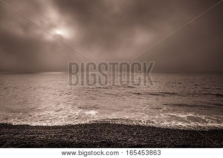 Dark, misty, foggy and cloudy dawn on the beach on the English coast in Hastings