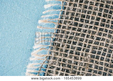 Combined background of light blue linen fabric and sackcloth. Macro view