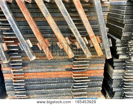 metal materials stacked at a shipping yard with rusty colors and silver colors.  Linear barricades stacked