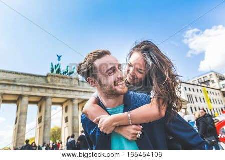 Happy couple having fun in Berlin. Mixed race couple a caucasian man giving a piggyback ride to his girlfriend an asian woman. Happiness lifestyle and tourism concepts