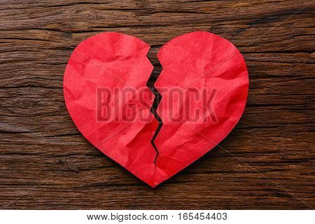 man hand holding a red paper broken heart on wooden background
