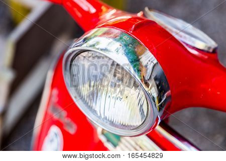 the headlight of red motorcycle, close up