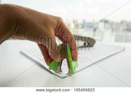 close up woman pull staple from business documents by staple remover