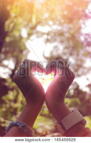 hand in shape of heart for love with blurred background