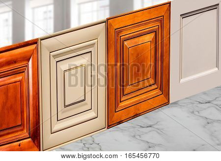 A set of cabinet kitchen doors, kitchen, bathroom, furniture or colset wall and base cabinets. A double and a single door made in wood on white marble counter top. Background blurry windows.
