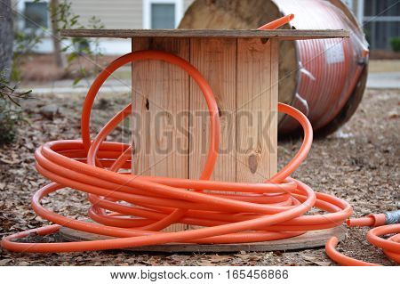 orange fiber cable on wooden spool neighborhood installation