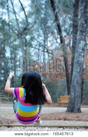little girl black hair striped dress on park swing
