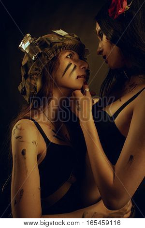 Glamour girl in underwear posing with another girl in helmet over dark background