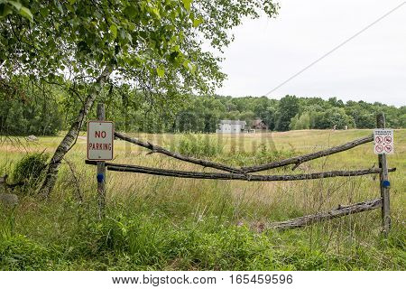 A broken wooden gate made of two thin logs at an edge of a field with a