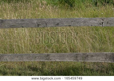A part of a section of an old weathered wooden countryside fence.