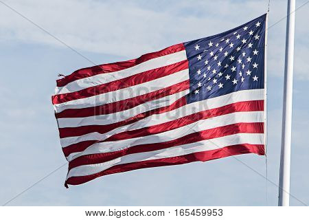 An American flag is flapping in the wind on a summer day.