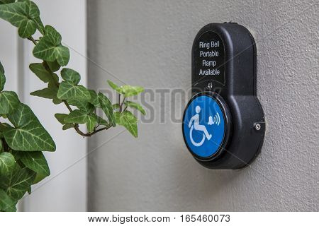 Portable wheelchair ramp bell button on a wall.