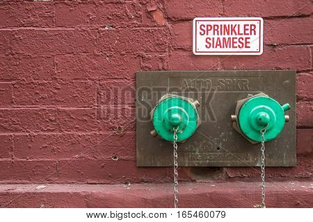 Siamese sprinkler connection in a painted brick wall.
