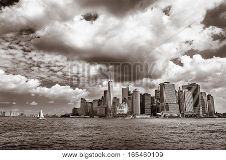 A small sailboat is cruising in New York harbor with the office buildings of lower Manhattan in the background.