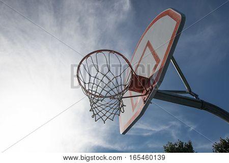 A suburban basketball hoop against blue sky.