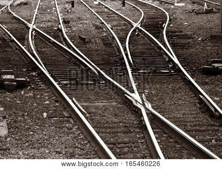 Railroad tracks branching out, black and white.