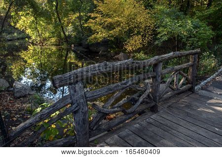 A picturesque wooden bridge in Central Park, NYC.