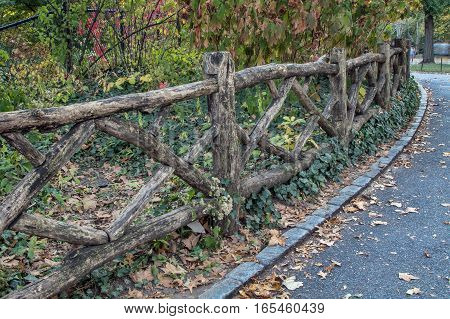 Wooden fence next to a paved path in Central Park.