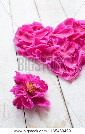 view from above of red peonies petals in heart shape as love symbol for wedding or valentines day decorate on wooden board background