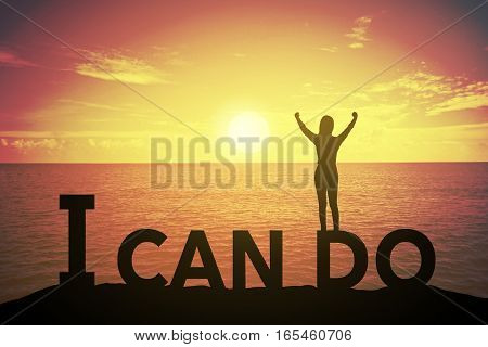 Silhouette young woman standing and raising up her hand about winner concept at I CAN DO text over a beautiful sunset or sunrise at the sea. background for success in 2017 years .hope to business success