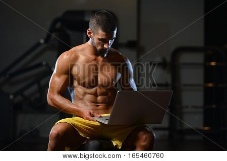 Muscular Athletic Bodybuilder Fitness Model Use Computer