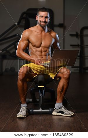 Portrait Of A Physically Fit Man Using Laptop