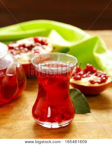 Fruit pomegranate tea in a teapot and cup