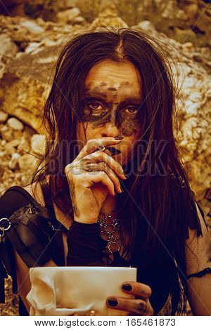 Sad post-apocalyptic raider smoking cigarette over rocks