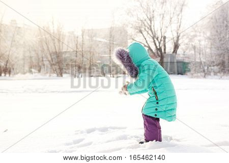 A cute little girl making a snowball in winter park. Outdoor Activities.