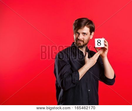Man holding a cube with the number eight. Numerals. A man shows a cube with the number eight