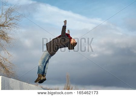 Man doing back flips. He is dressed in coat scarf jeans and gloves. Winter.