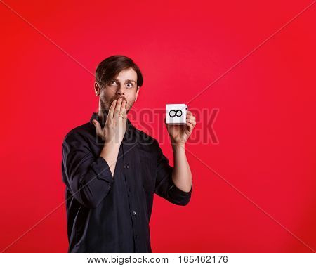 Man holding cube with the sign of infinity. Numerals. A man shows a cube with the sign of infinity. He was surprised and covers her mouth.
