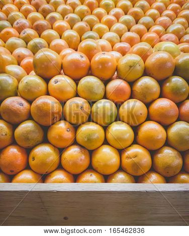 Stack of Oranges on Fruit Shelf Stand with Wood for Copy Space at bottom
