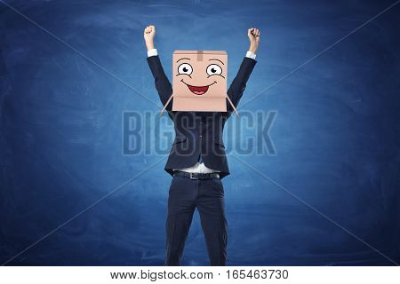 Businessman with hands raised in victory and wearing a carton box with drawn happy face on blue blackboard background. Business and management. Workplace communication. Fitting in.