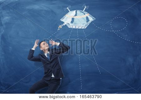 A businessman frightened by a flying saucer painted on a blue blackboard behind him. Stress on work. Under pressure. Business failure.
