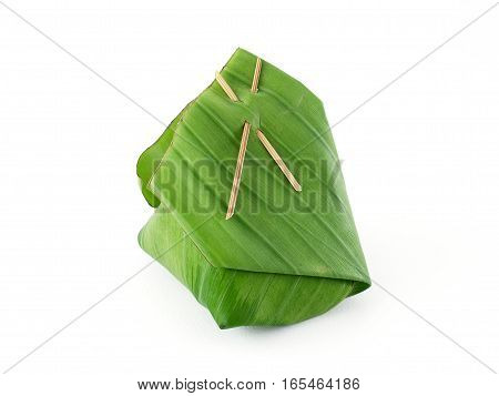 close-up thai dessert packaging isolated on white background, banana leaf wrapped dessert which is usually made of sticky rice, traditional thai food package (environmentally friendly packaging)