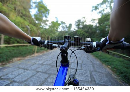 hands riding mountain bike on forest trail