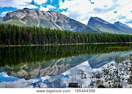 Crystal clear water in alpine lake and reflections of mountains and clouds. Honeymoon lake in Canadian Rocky Mountains. Jasper National Park. Alberta. Canada.